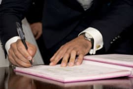 man-signing-papers
